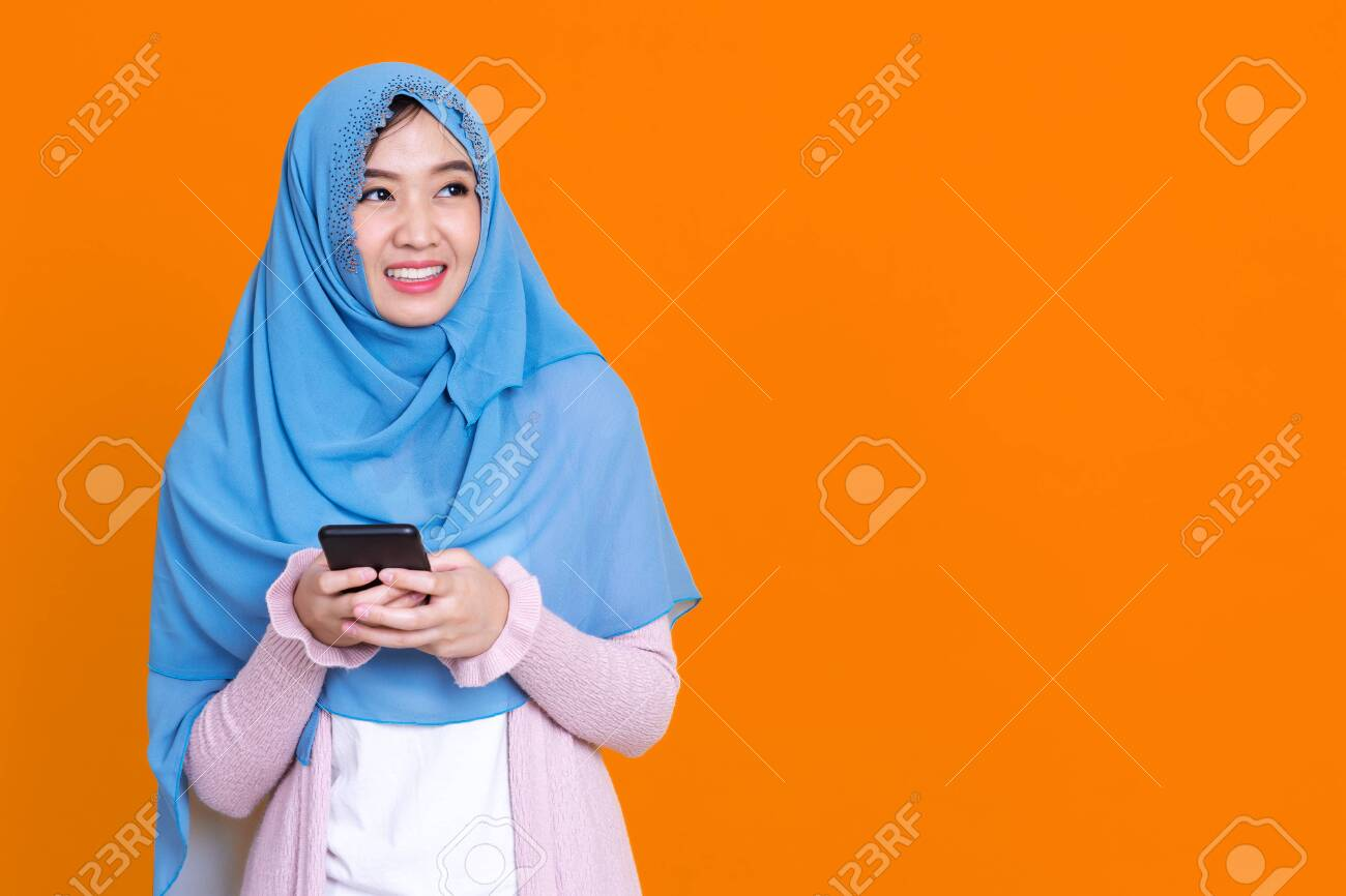 Photo of islamic woman in hijab headscarf wearing mask with oriental makeup use smartphone and credit card over orrange isolate background - 148856618