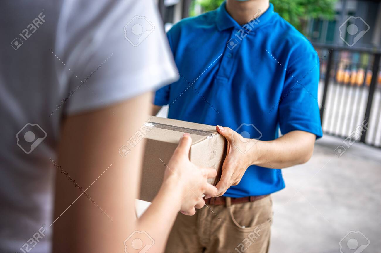 Asian deliveryman is delivering parcel to house her to sign to receive the product After she ordered online during the outbreak of the coronavirus or Covid-19 virus. - 148855843