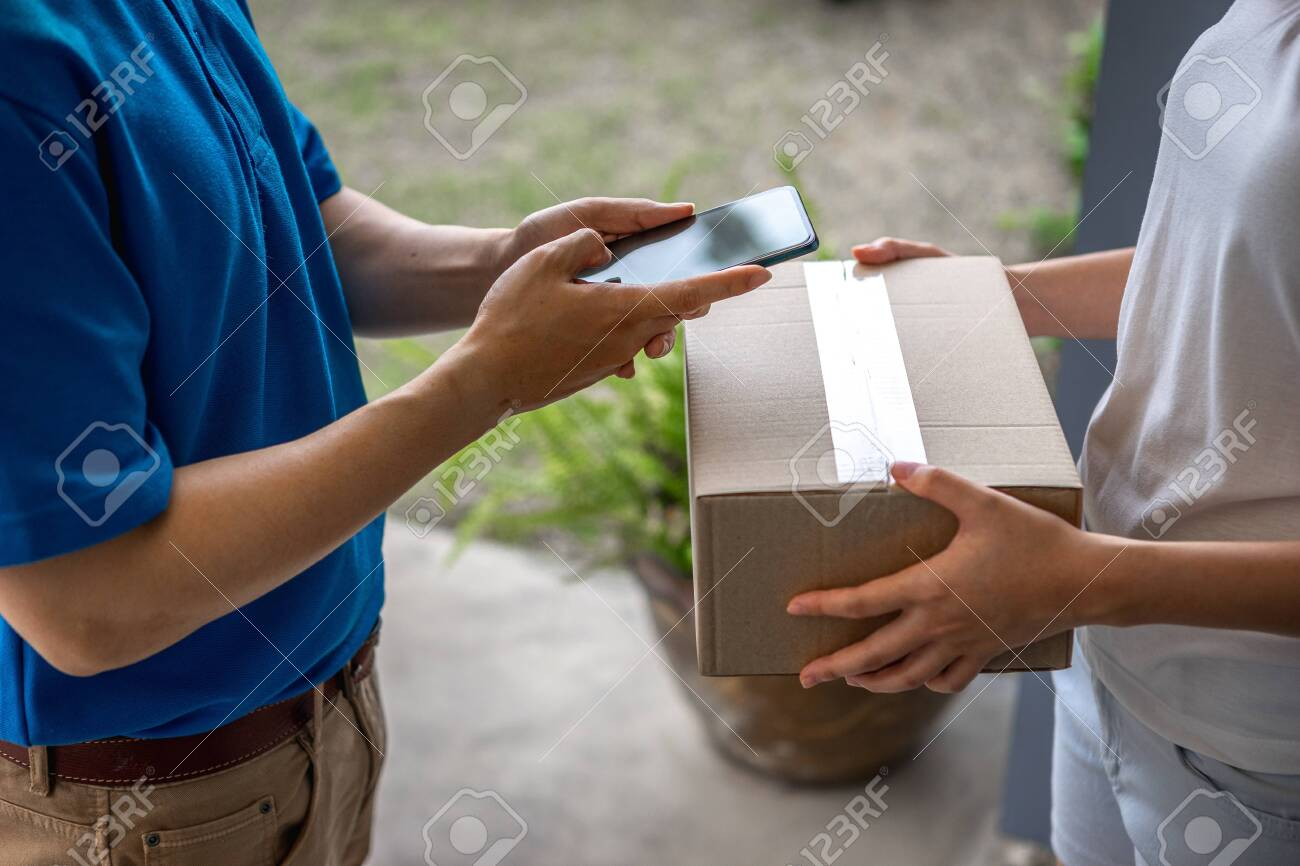 Asian deliveryman is delivering parcel to house her to sign to receive the product After she ordered online during the outbreak of the coronavirus or Covid-19 virus. - 148855844
