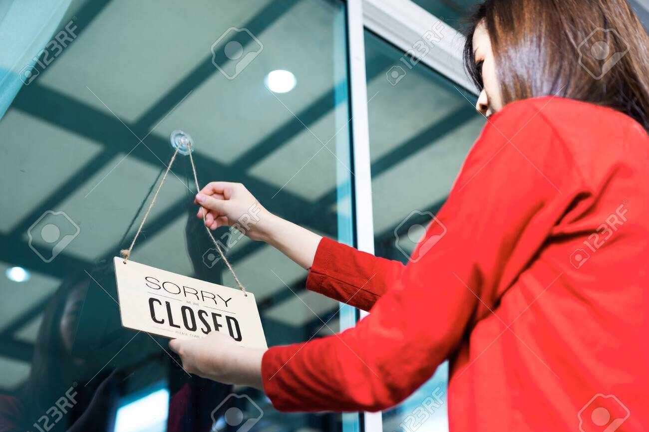 Asian woman shop owner hanging label 'Sorry we are Closed'. She close her shop under pandemic coronavirus - 149473795
