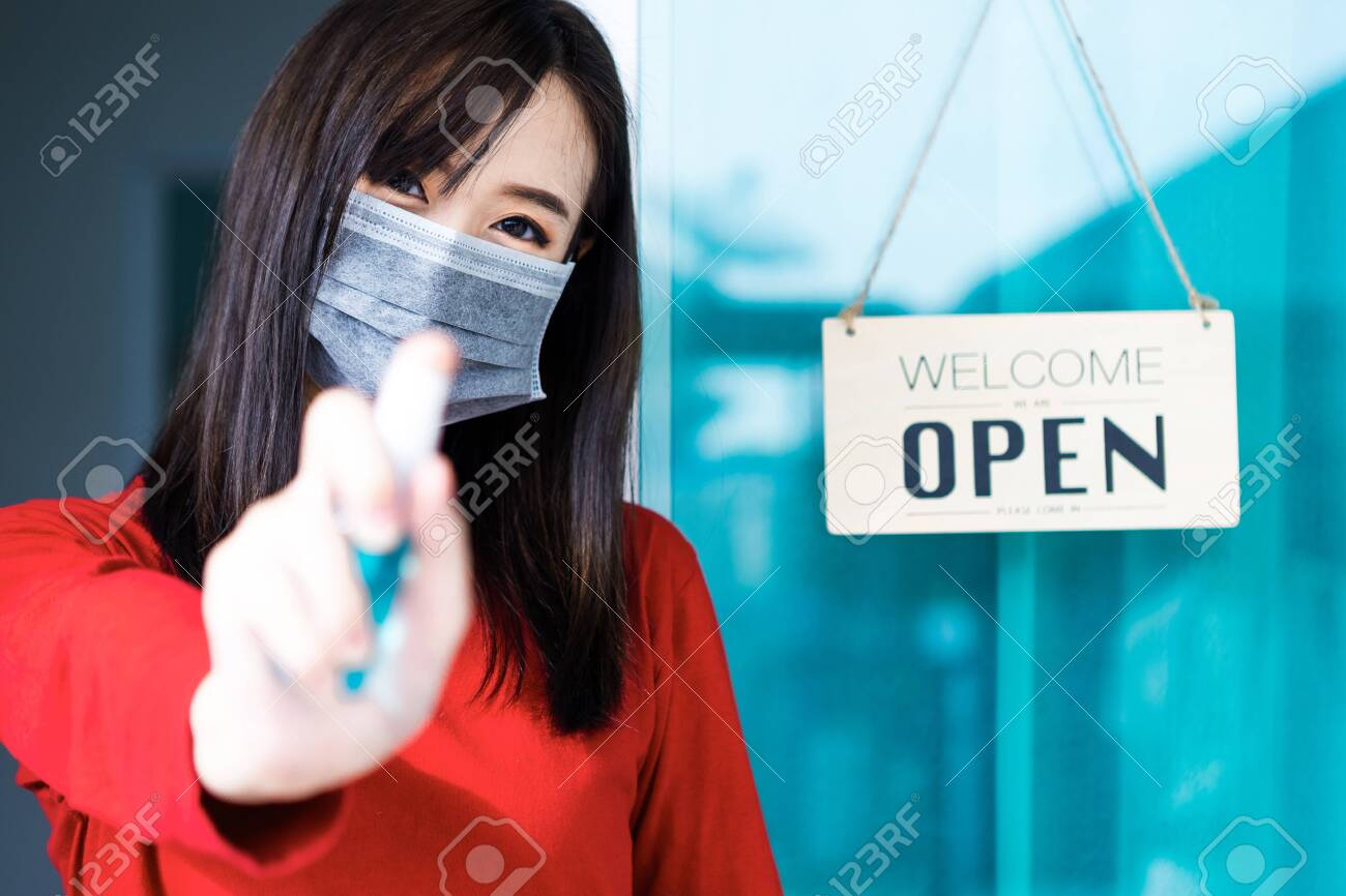 Asian woman shop owner smiling hanging label 'Welcom we are open' and showing thump up. She open her shop after pandemic of coronavirus outbreak - 149473799