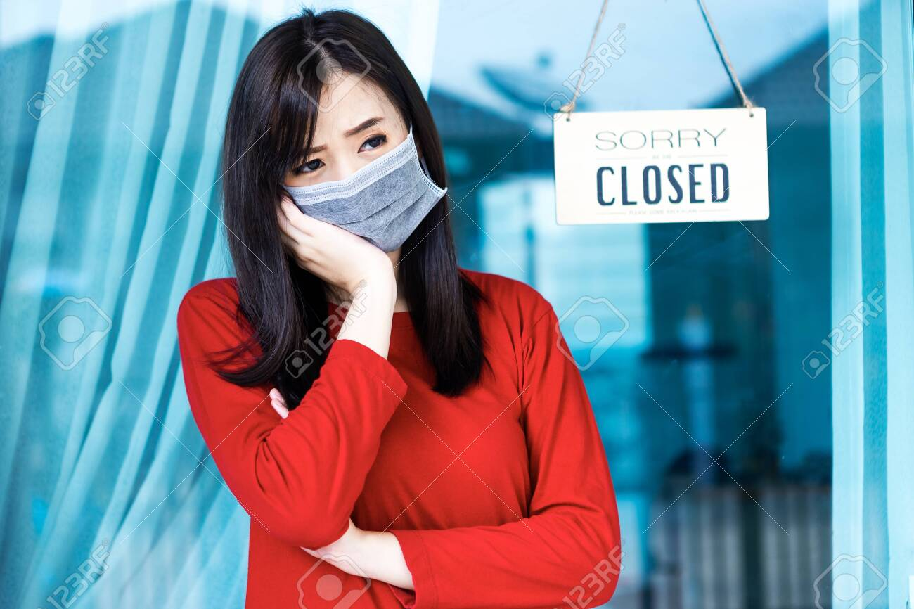 Asian woman shop owner hanging label 'Sorry we are Closed'. She close her shop under pandemic coronavirus - 149473802