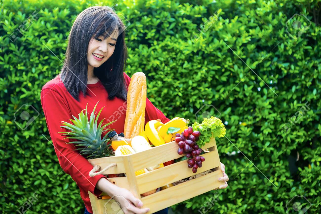 Asian woman holding wooden basket with vegetables. fresh vegetables in a basket. picnic in the garden. Stay at home. Enjoy cooking at home. Family concept. - 149143987