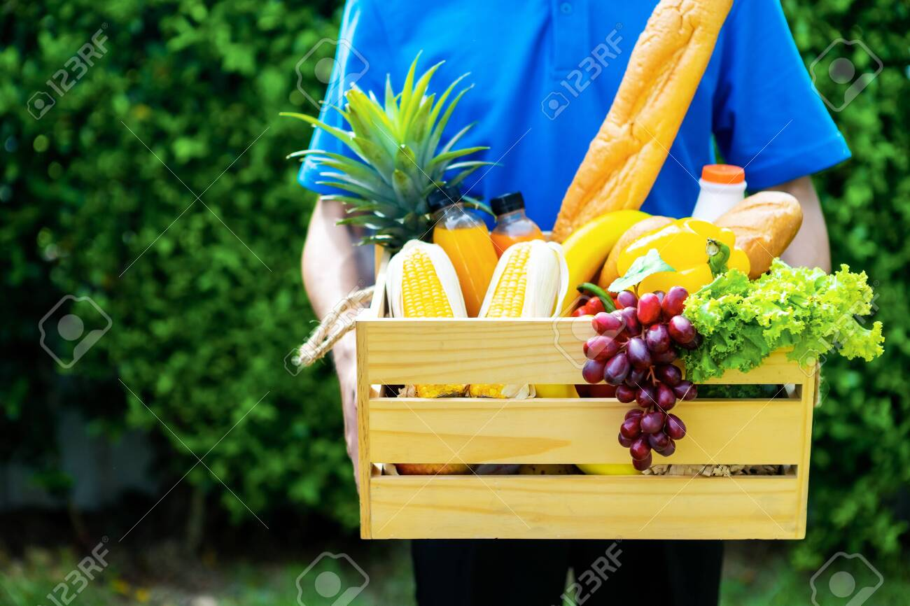 Asian delivery man blue uniform wearing medical face mask making grocery service giving fresh food to customer receiving front house, Food delivery and grocery service concept. - 149473805