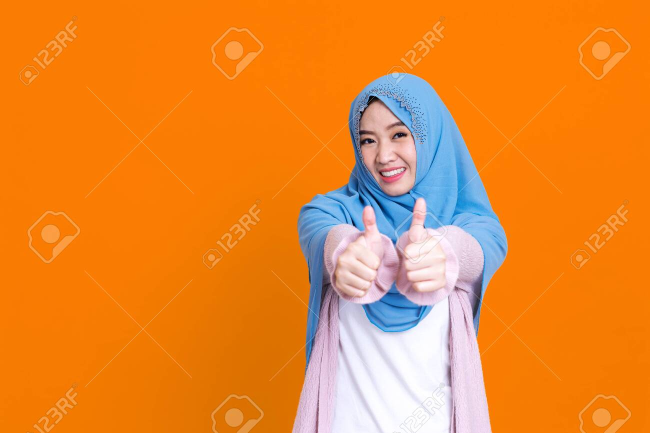 Happy muslim Asian woman showing thumb up gesture over color isolated background. - 149473859