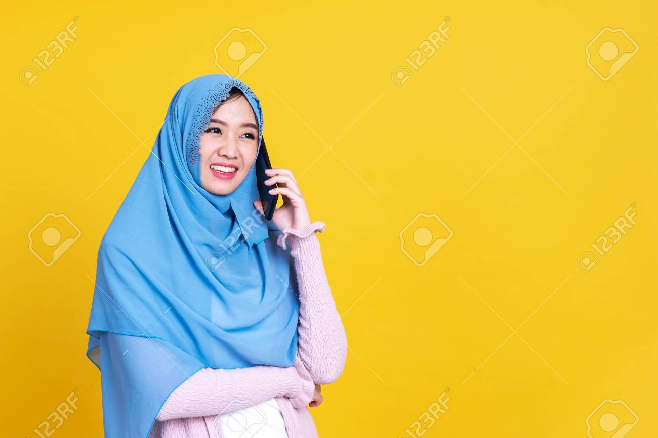 Smiling Asian muslim woman with using mobile or smartphone over isolated color background. - 149473867