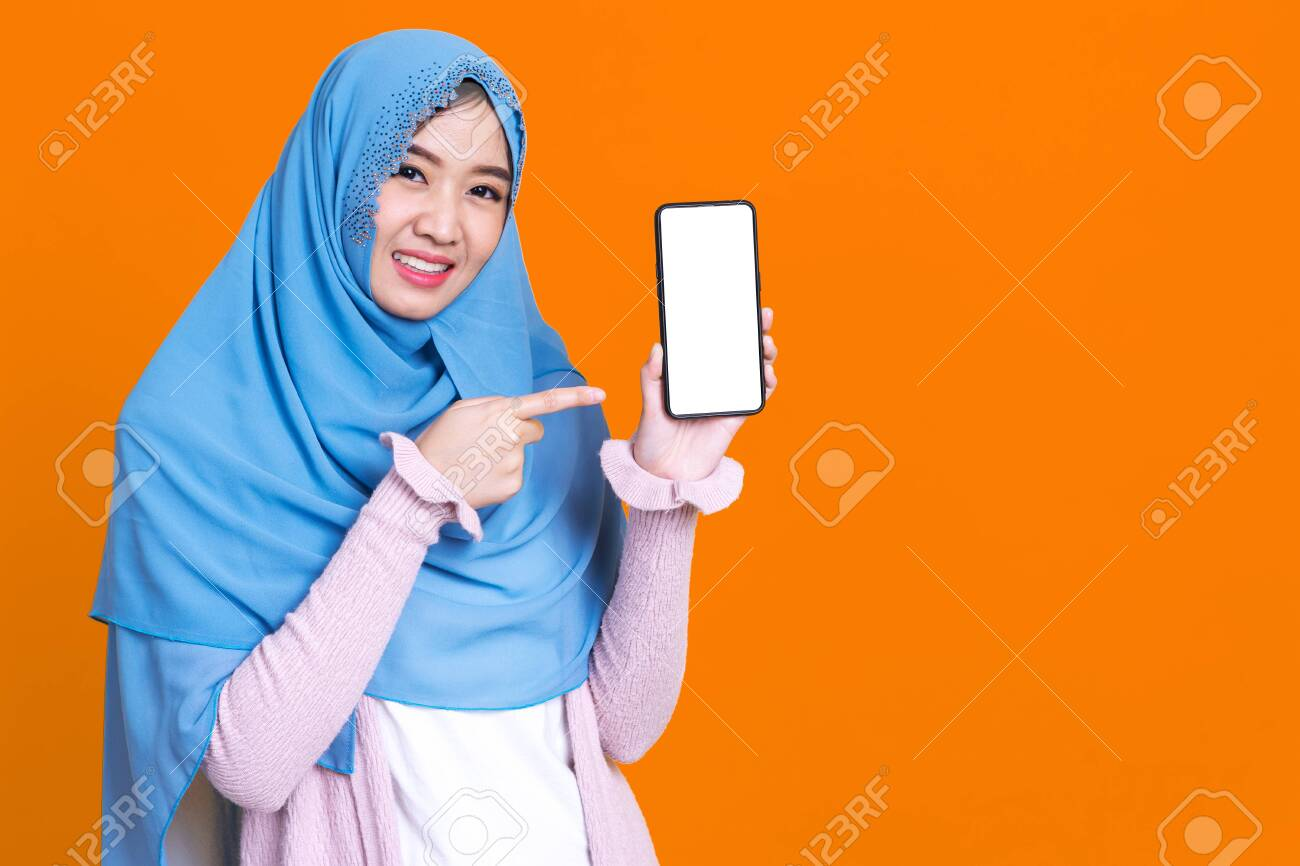 Muslim asian woman showing blank mobile phone screen over isolated color background. - 149473869