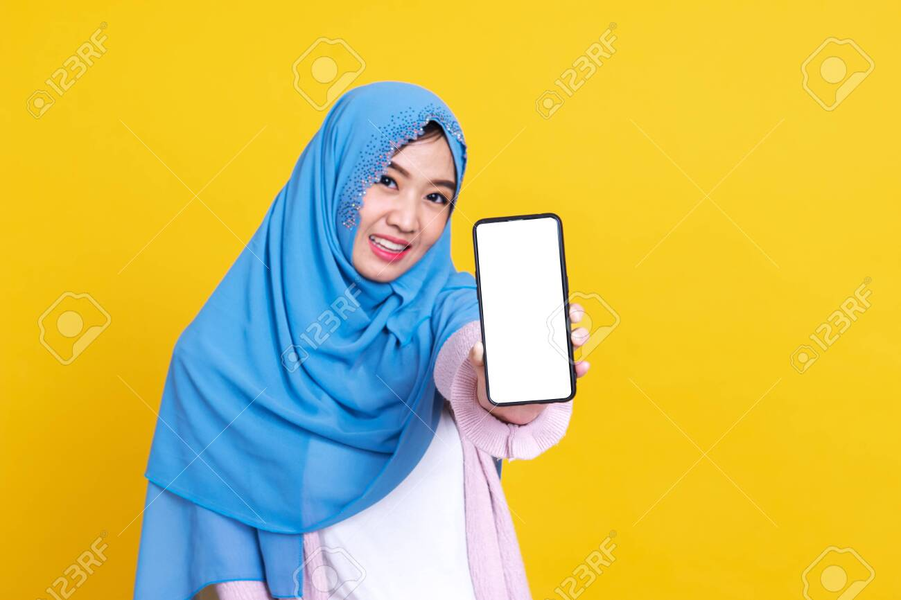 Muslim asian woman showing blank mobile phone screen over isolated color background. - 149473870