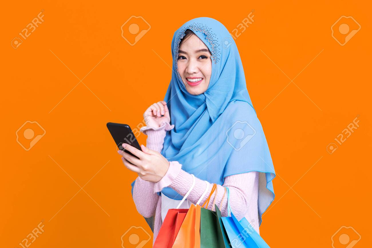 Muslim woman holding shopping bag using mobile phone and credit card isolated color background. - 149473875