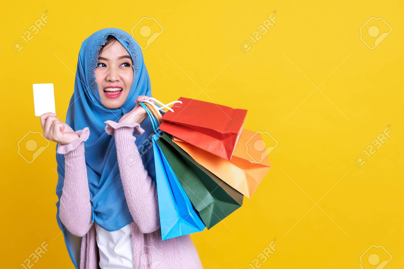Muslim woman holding shopping bag using mobile phone and credit card isolated color background. - 149473876