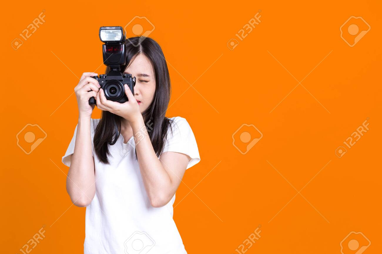 Portrait photo of Asian smiling pretty girl in white shirt taking photo on camera isolated over color background - 149473878