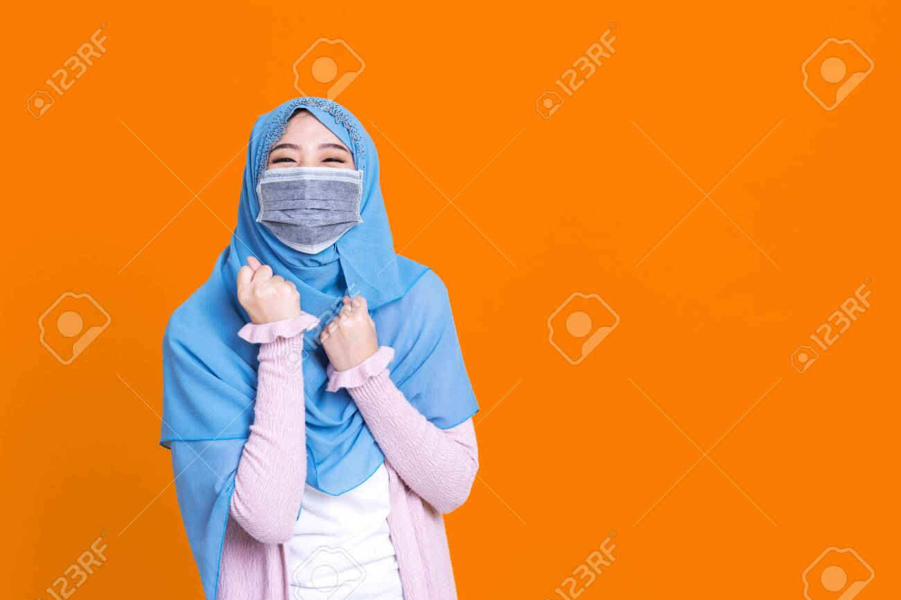 Asian muslim woman wearing hijab and medical mask over isolated background celebrating surprised and amazed for success with arms raised and open eyes. Winner concept. - 149473926