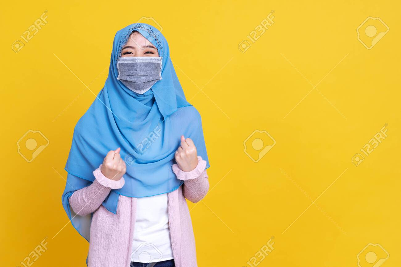 Asian muslim woman wearing hijab and medical mask over isolated background celebrating surprised and amazed for success with arms raised and open eyes. Winner concept. - 149473934