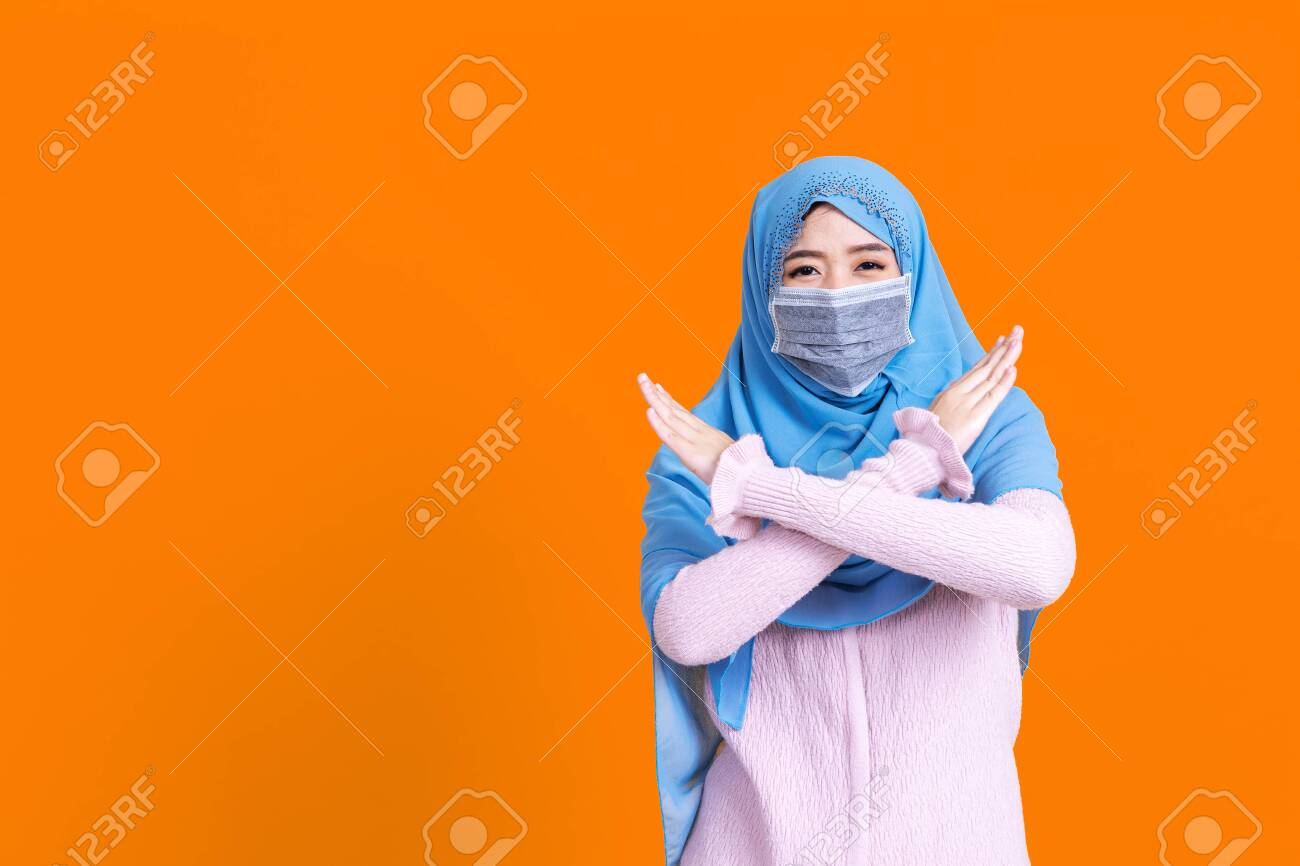 Asian serious muslim woman wears hijab, makes cross with hands over chest, shows stop or prohibition gesture, disagrees with uninteresting offer, isolated over blue background. No sign - 149473937