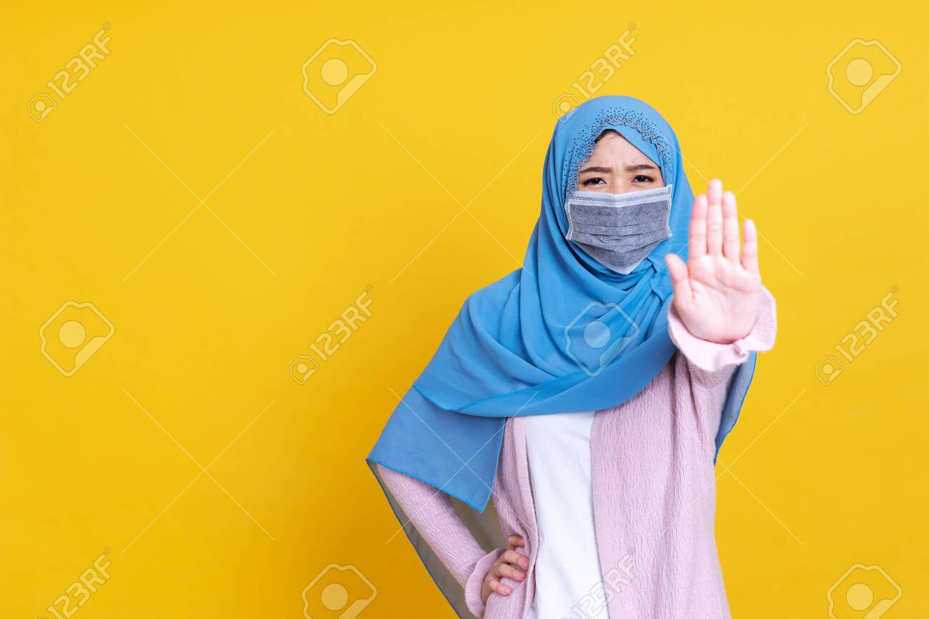 Asian serious muslim woman wears hijab, makes cross with hands over chest, shows stop or prohibition gesture, disagrees with uninteresting offer, isolated over blue background. No sign - 149473939