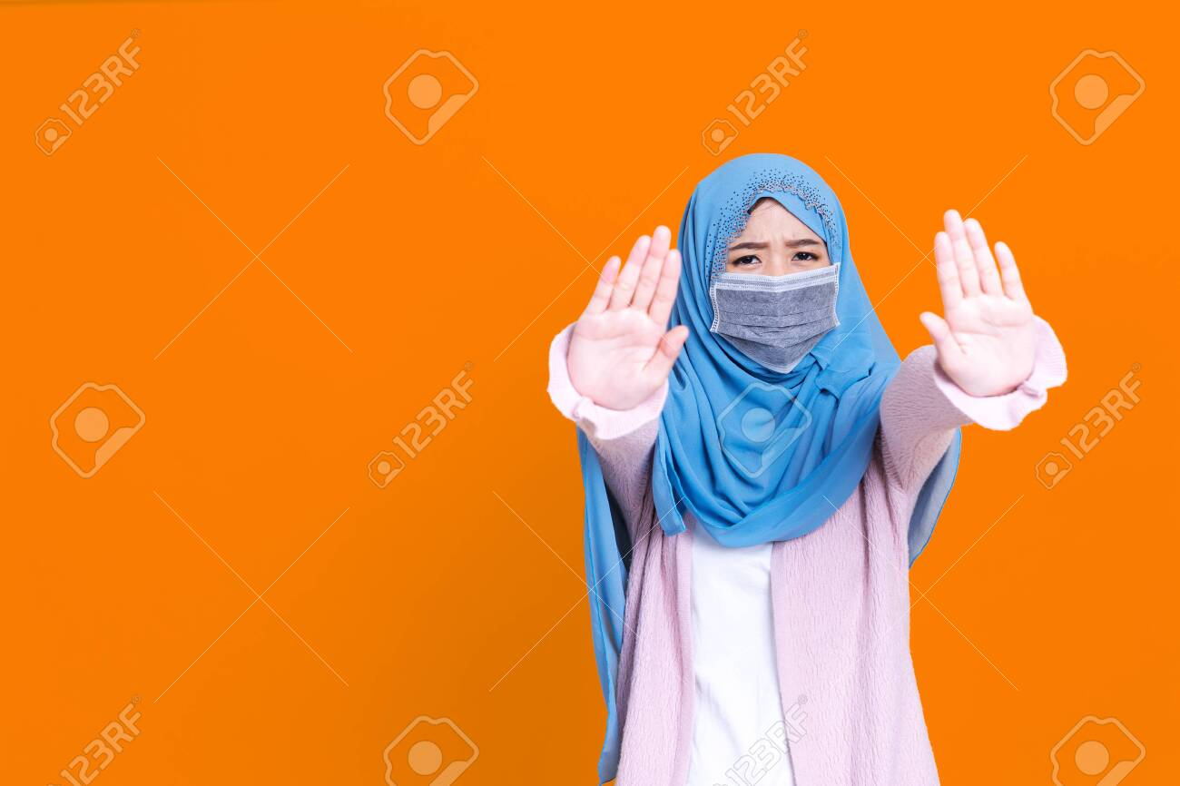 Asian serious muslim woman wears hijab, makes cross with hands over chest, shows stop or prohibition gesture, disagrees with uninteresting offer, isolated over blue background. No sign - 149473940