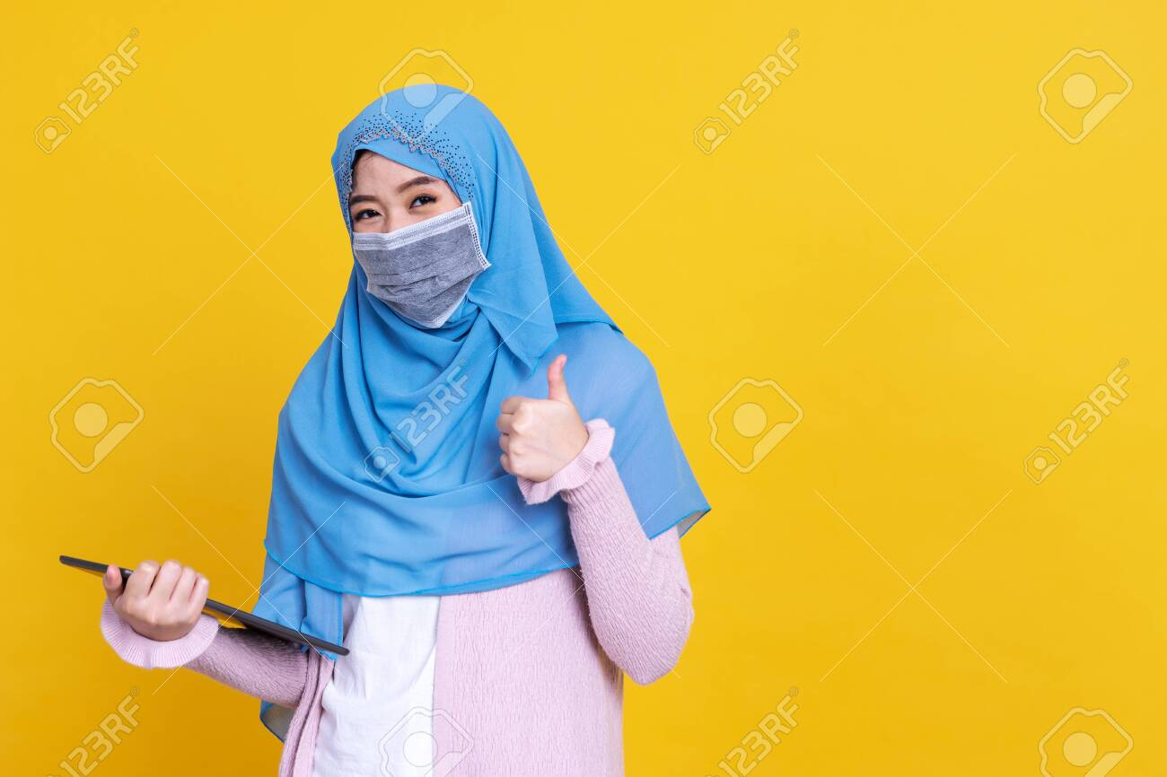 Asian Muslim woman wearing medical mask in hijab and using digital tablet isolated on color background - 149473941