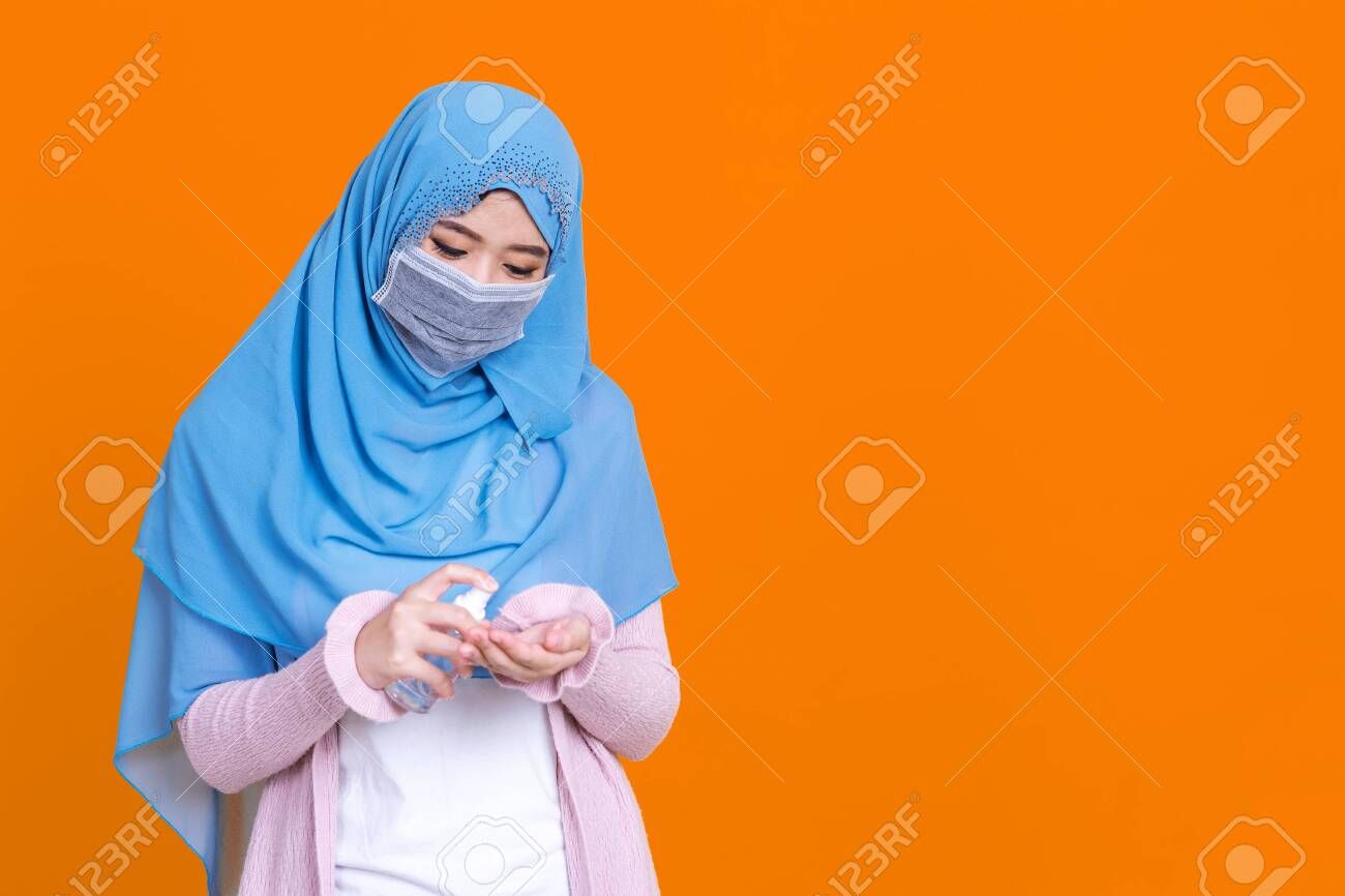 Muslim asian woman with traditional dress wearing medical face mask under the outbreak of the virus,Wash her hands with an alcohol gel isolated on color background - 149473945