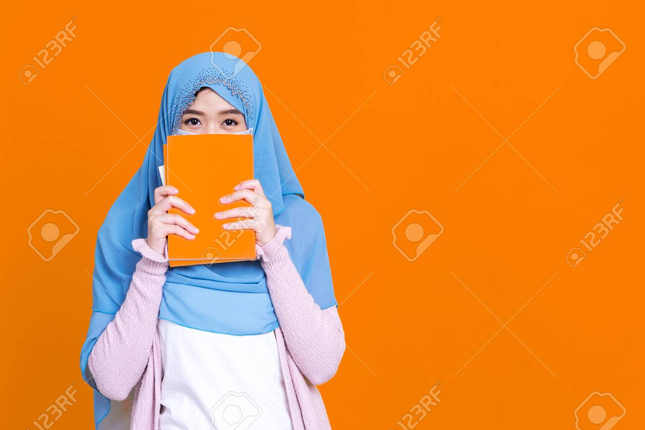 Asian muslim woman in hijab and wearing medical mask and holding book over isolate color background. Education concept. - 149473953