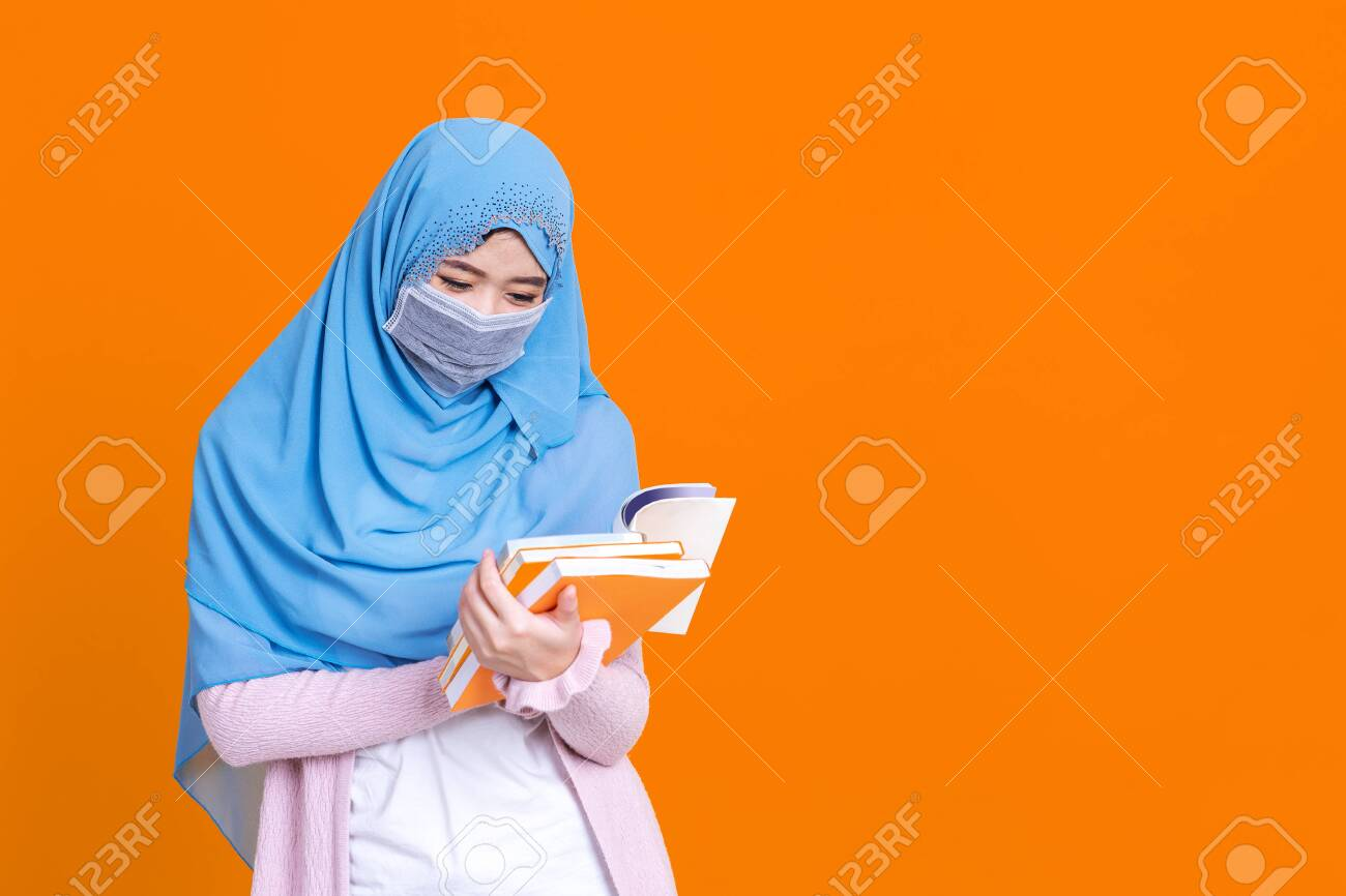 Asian muslim woman in hijab and wearing medical mask and holding book over isolate color background. Education concept. - 149473956