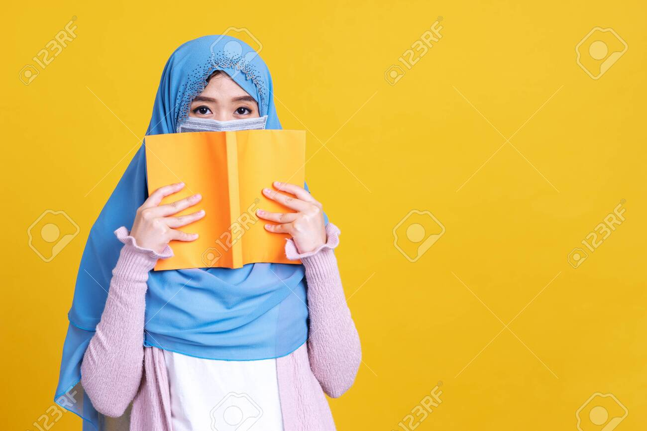 Asian muslim woman in hijab and wearing medical mask and holding book over isolate color background. Education concept. - 149474068