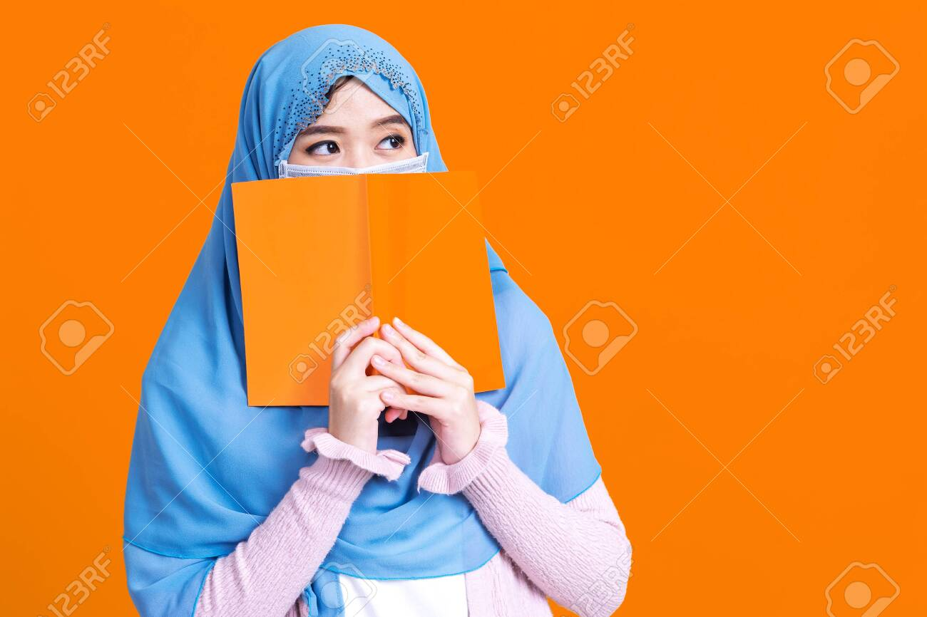 Asian muslim woman in hijab and wearing medical mask and holding book over isolate color background. Education concept. - 149474071