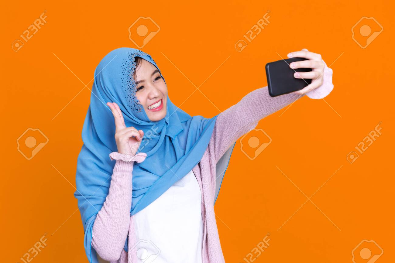 Happy Asian muslim woman taking selfie with smartphone isolated on color background - 149474077