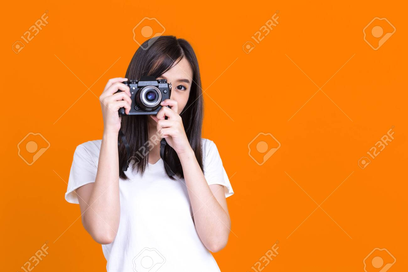 Asian woman smiling pretty girl in white shirt taking photo on camera isolated over color background - 149474083