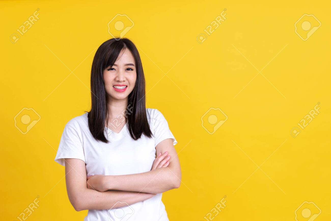 Beauty smiling brunette Asian woman pointing away and smiling and looking at the camera over yellow background - 149399106