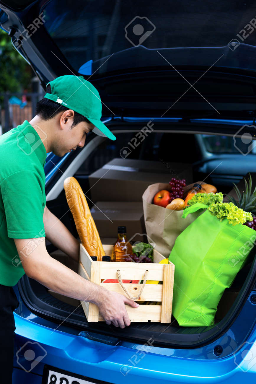 Asian delivery man in green t-shirt delivering food, fruit, joice and vegetable to home - online grocery shopping service concept - 151862893