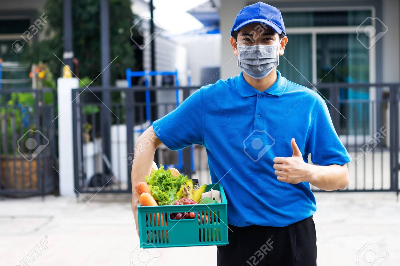 Asian delivery man blue uniform wearing medical face mask making grocery service giving fresh food to customer receiving front house, Food delivery and grocery service concept. - 151862894