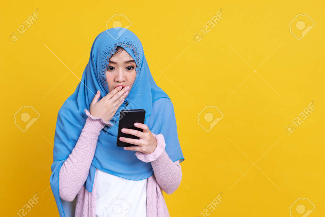 Smiling Asian muslim woman with using mobile or smartphone exciting over isolated color background. - 151863012