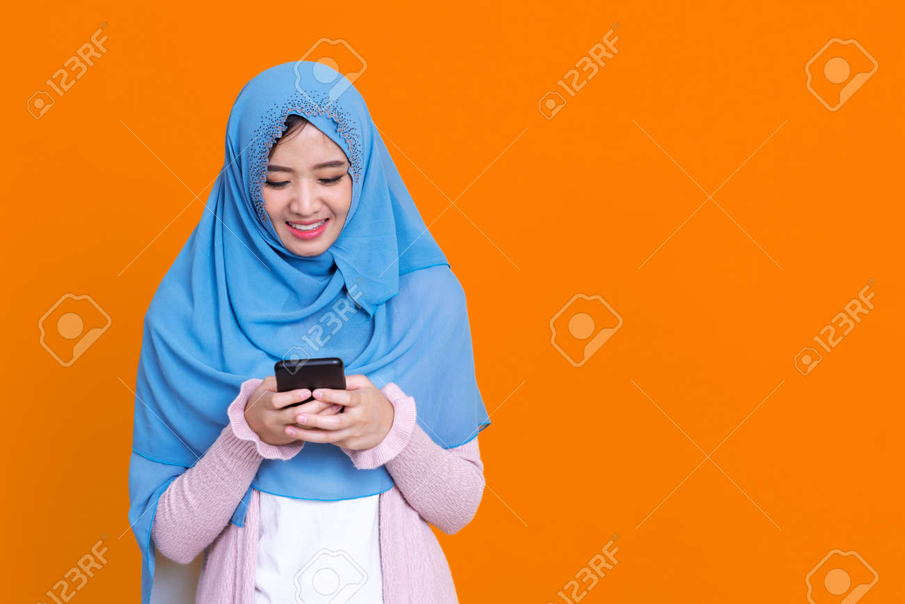 Smiling Asian muslim woman with using mobile or smartphone exciting over isolated color background. - 151863060