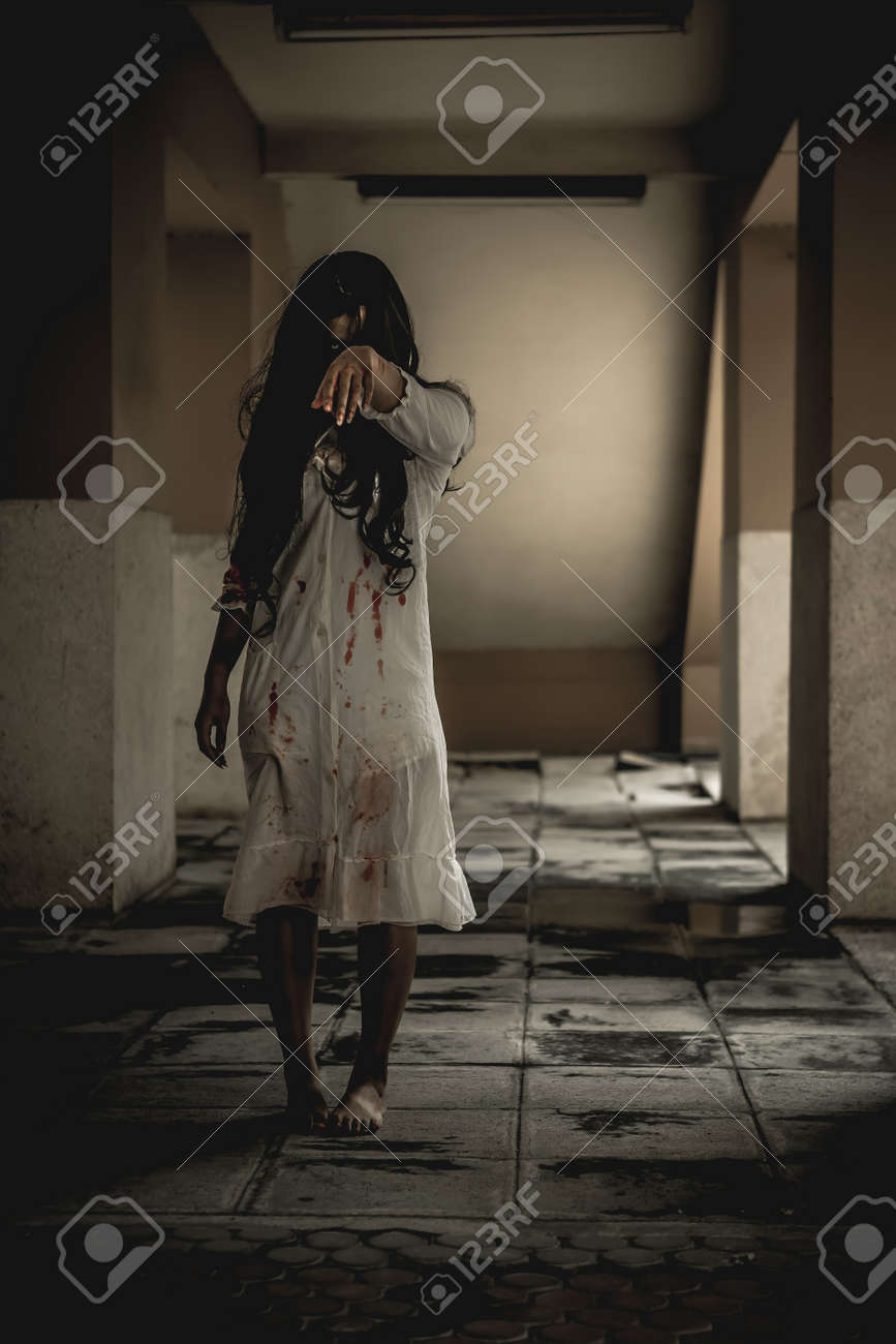 Woman in ghost or zombie on halloween festival at dark place, holding knife and wants to stab you. Horror or halloween festival concept. - 157438637