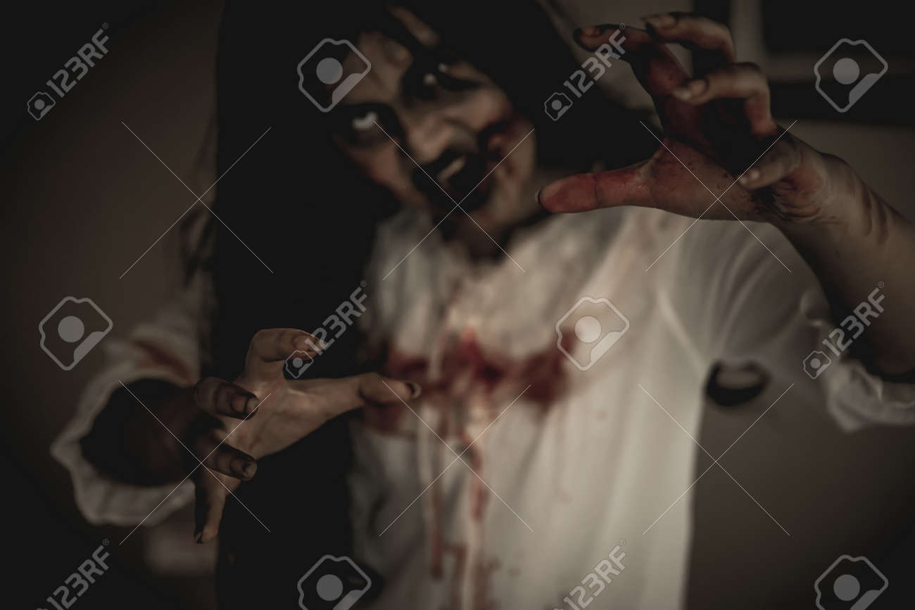 Woman in ghost or zombie on halloween festival at dark place, holding knife and wants to stab you. Horror or halloween festival concept. - 157438638