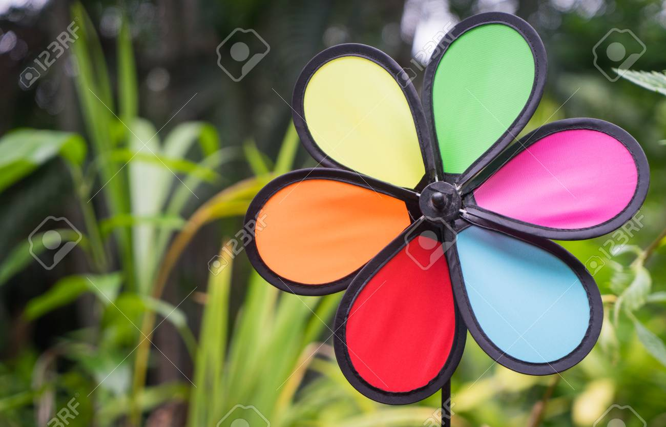 Colorful Toy Wind Turbine In Green Garden Background Stock Photo