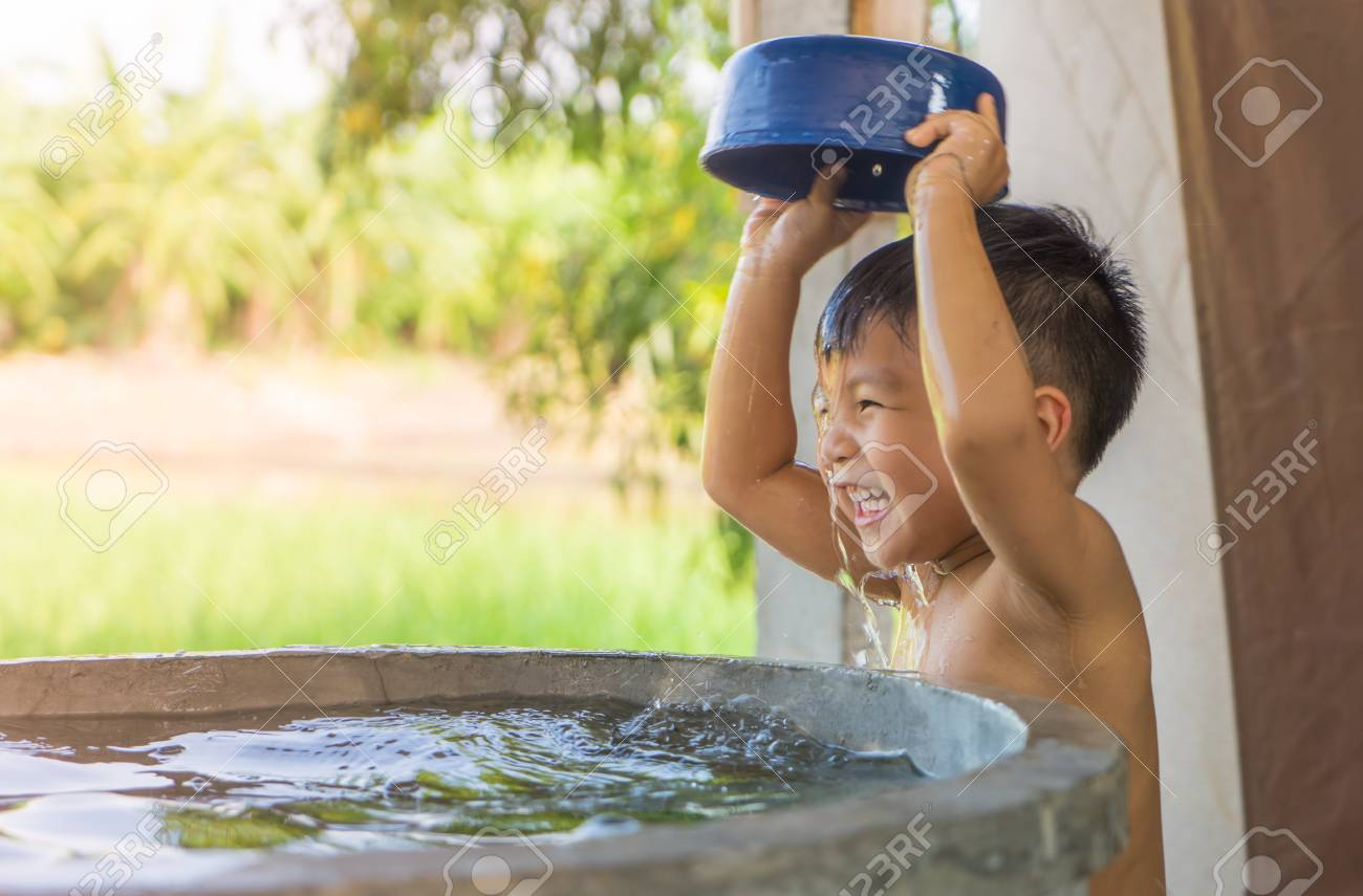 Asian Village poor boy is taking a bath from village water well