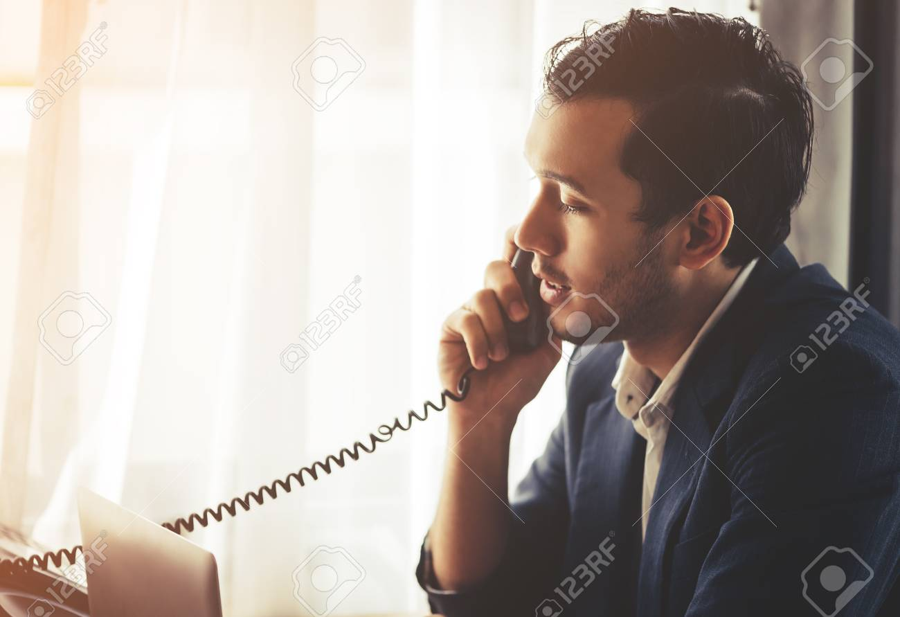 Business man is making call in on Fax phone landline - 102173761