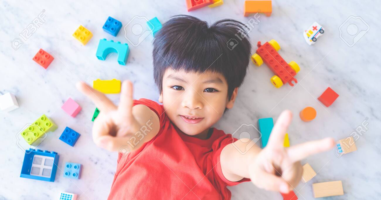 Happy boy surrounded by colorful toy blocks top view V shape hand for victory - 123203099