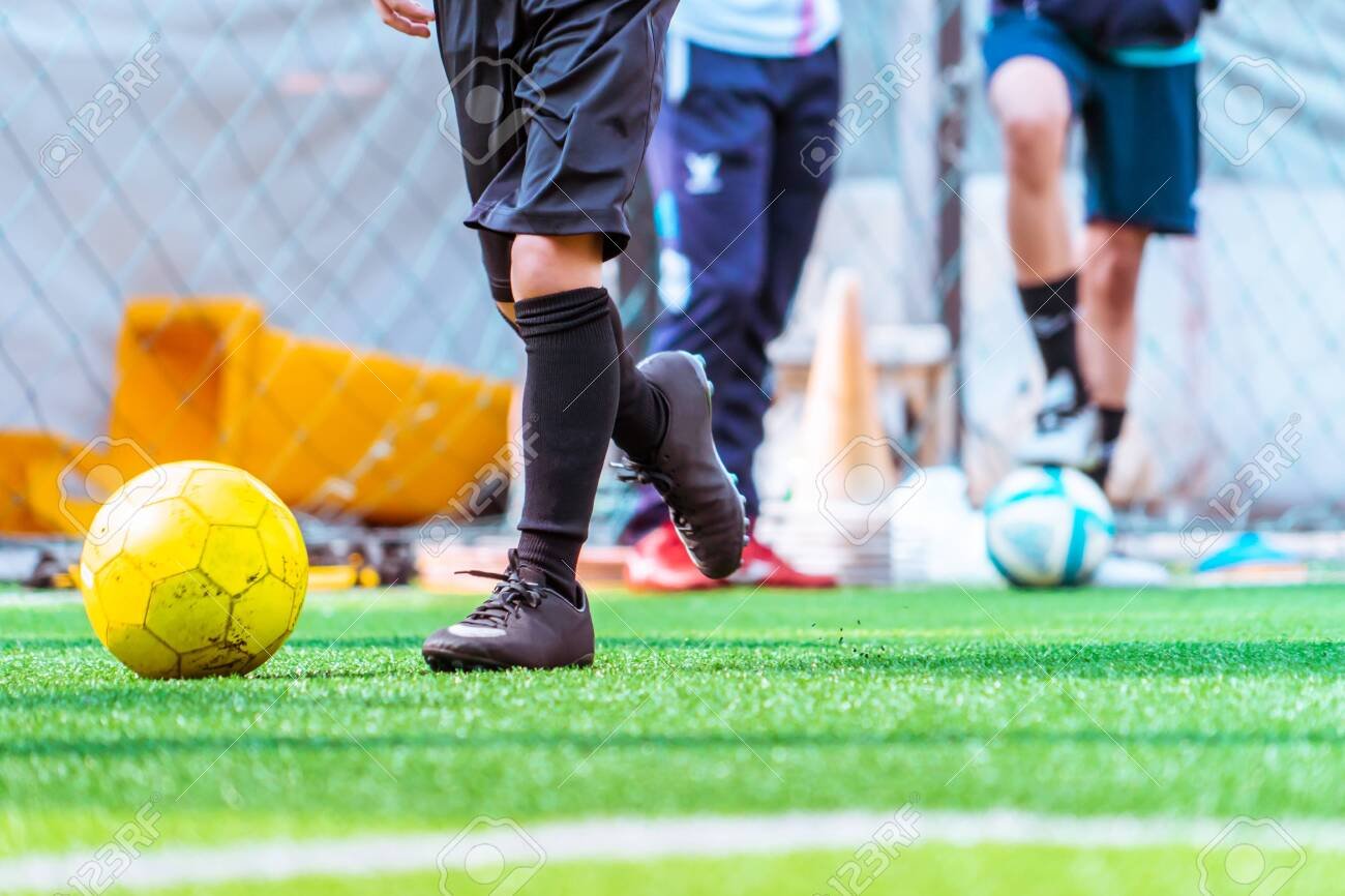 Children is training and dibbling ball in soccer training - 124374398