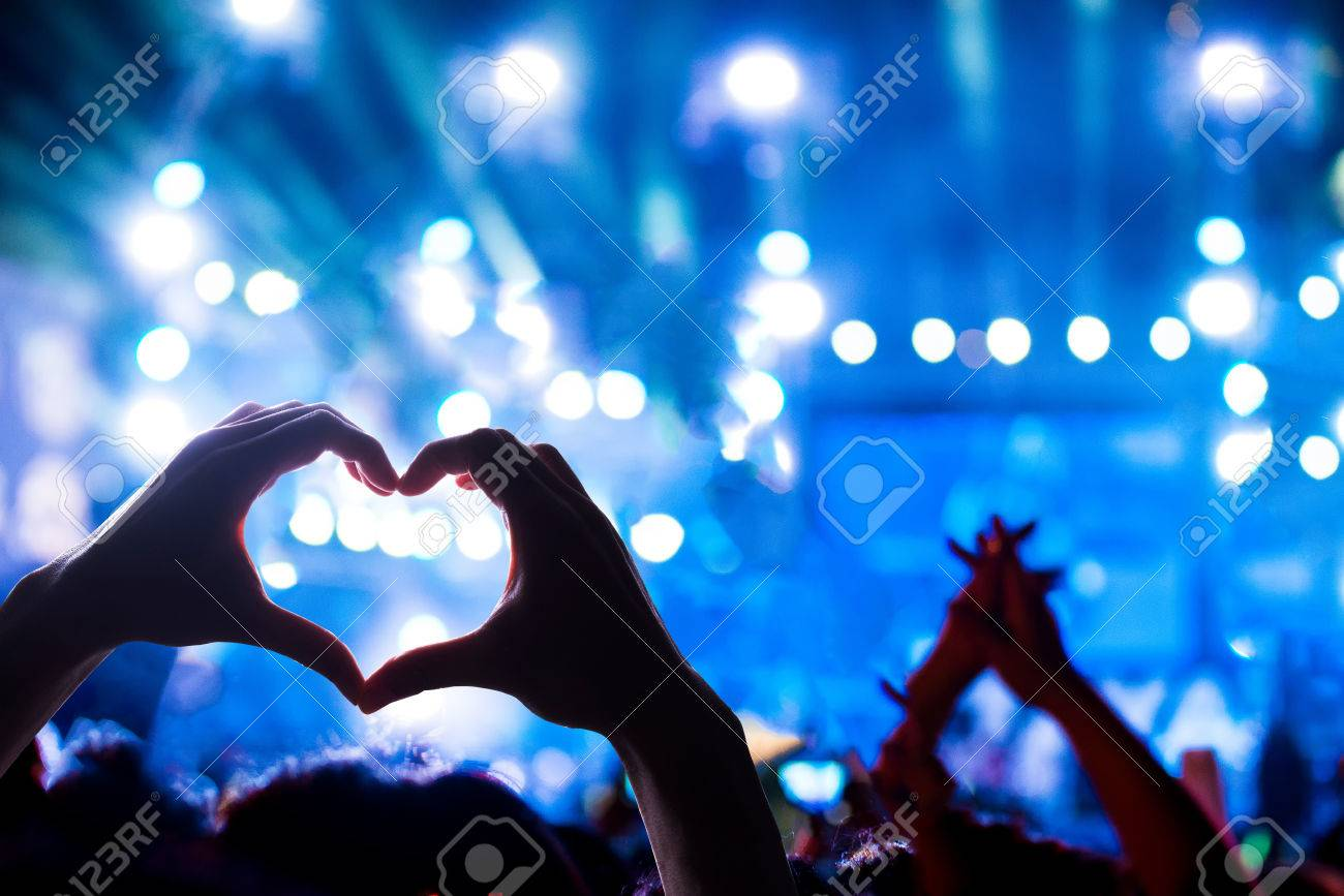 Crowd Of Audience At During A Concert With Silhouette Of A Heart Shaped  Hands Shadow,