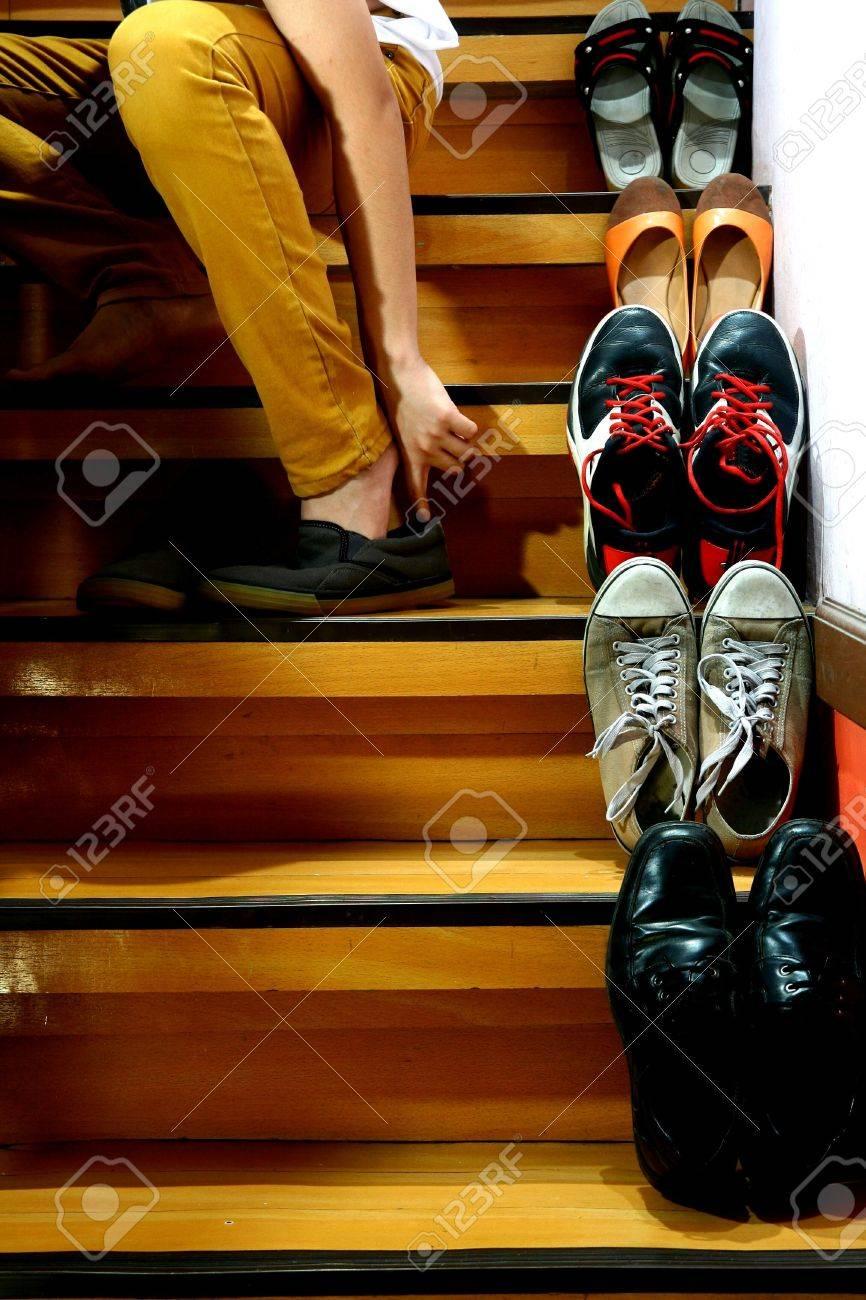 Banque d images - Personne mettre ses chaussures alors qu il était assis à  côté de chaussures différentes sur un escalier cebcd25caecc