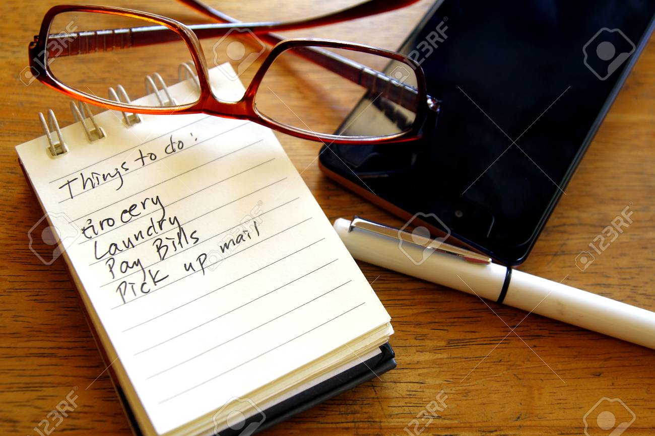 Checklist or to do list in a notebook, pen, eyeglasses and smartphone - 100221567