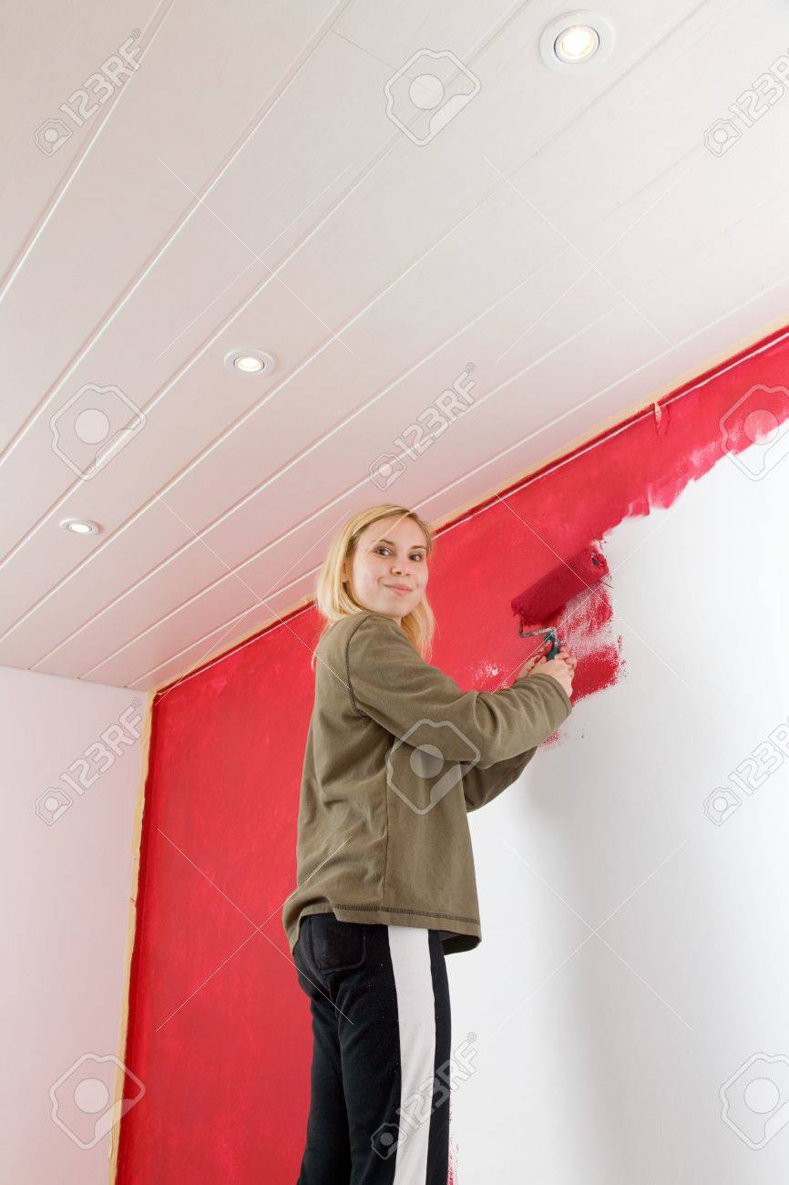 Girl painting a room in red color. Stock Photo - 6076238