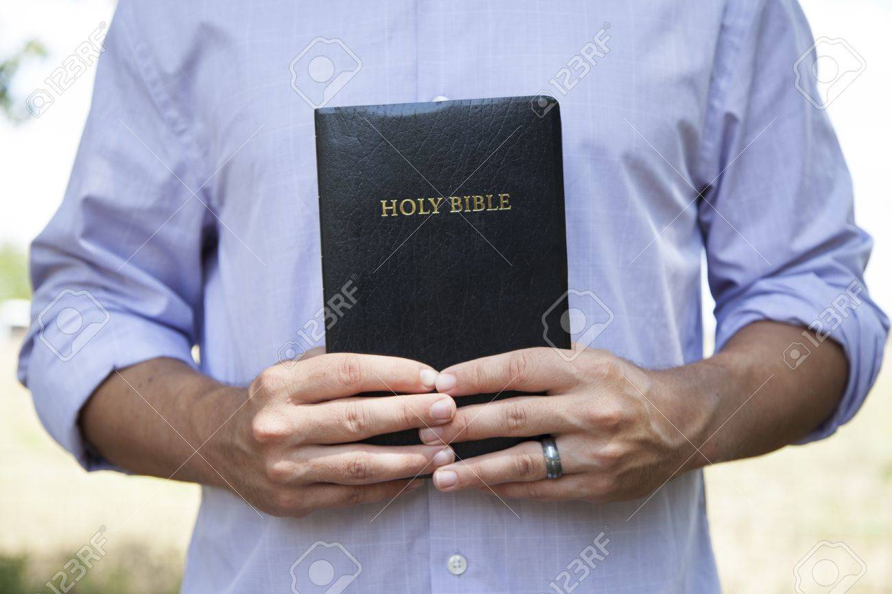 A man stands outside and holds a  black bible with both hands. Stock Photo - 14775472
