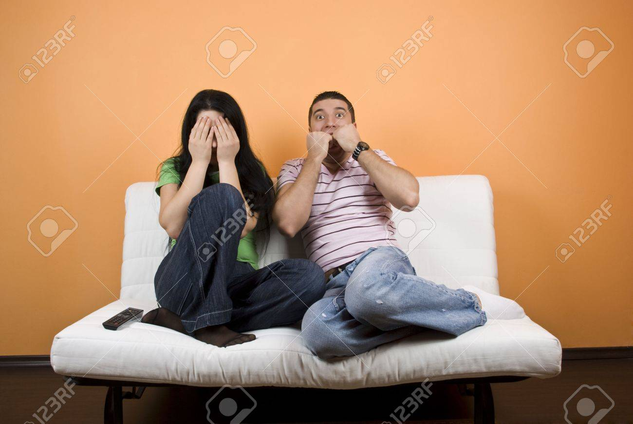 Couple watching TV a horror movie,woman cover eyes to not see anymore  while the young man are terrified Stock Photo - 4256668