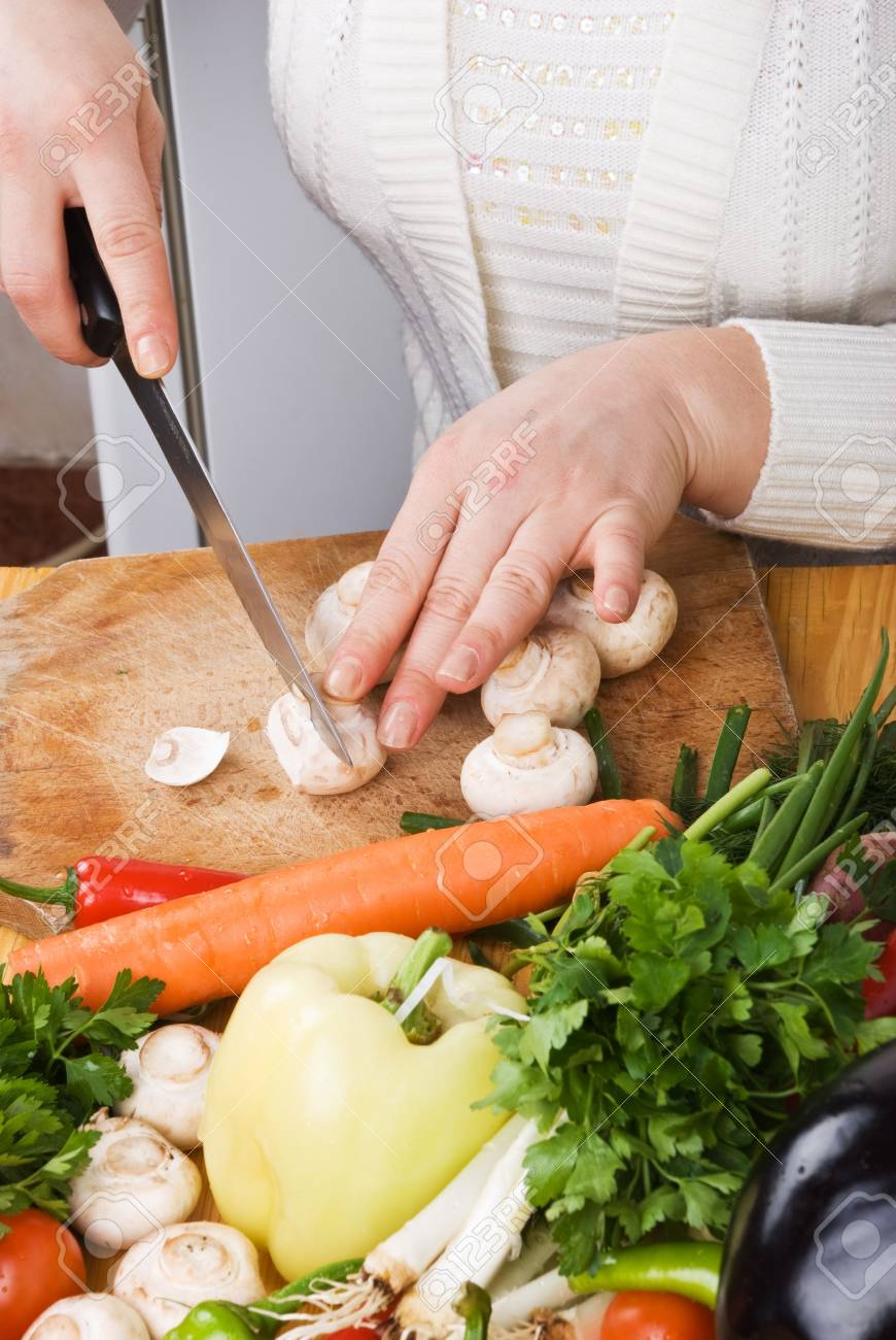 Woman in kitchen slicing  mushroom on wood board and variety of fresh vegetables Stock Photo - 4452515