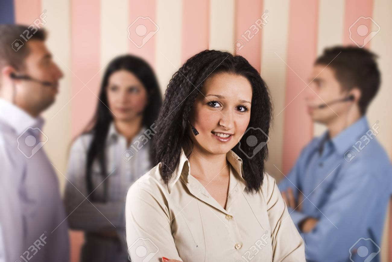 Beauty customer service young woman smiling in front of image with her team in background Stock Photo - 5527033