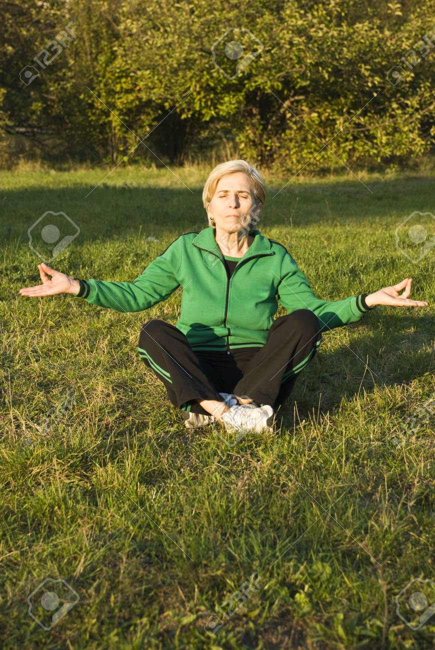 Senior woman doing yoga lotus position outdoors in the park Stock Photo - 5766094