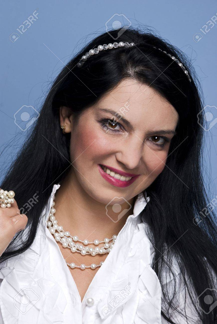 Close up of fashionable stylish woman dressed in white shirt with pearls and wearing a pearl band in her black hair on blue background Stock Photo - 5786911